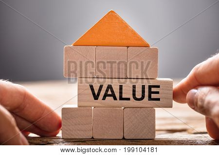 Closeup of hands building house model with value block on wood
