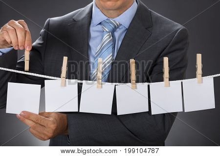 Closeup midsection of businessman pinning blank paper on clothesline