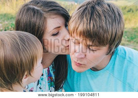 mother kiss father on cheek in front of daughter in summer day