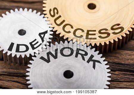 Closeup of success idea and work interlocked cogwheels on wood