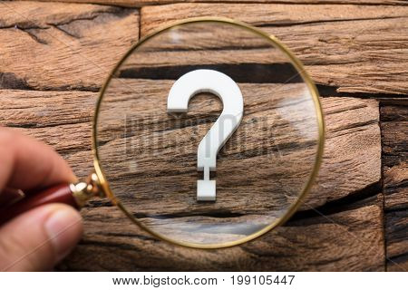 Closeup of hand holding magnifying glass over question mark on wood