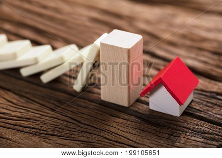 Closeup of wooden block amidst model house and domino pieces representing home insurance on table