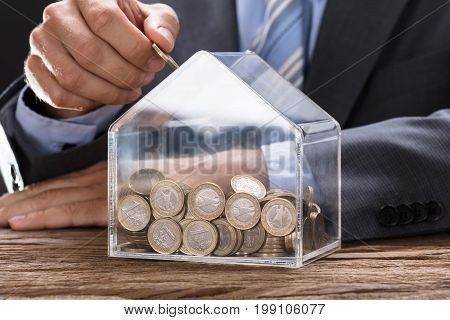 Midsection of businessman putting coin in transparent house shaped piggybank at wooden table