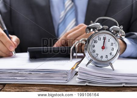 Midsection of businessman calculating invoice with alarm clock on documents at table