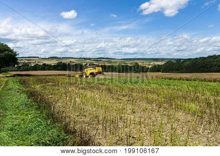 NEUSTADT GERMANY - JULY 30 2017: Harvesting on the fields in the suburbs of the small town of Neustadt (Marburg-Biedenkopf district in Hessen). Harvester on the field.