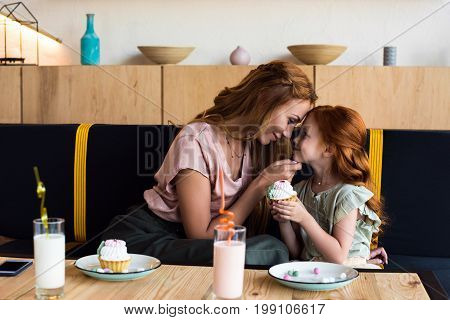 Happy Mother And Daughter Touching Foreheads While Eating Cupcakes In Cafe