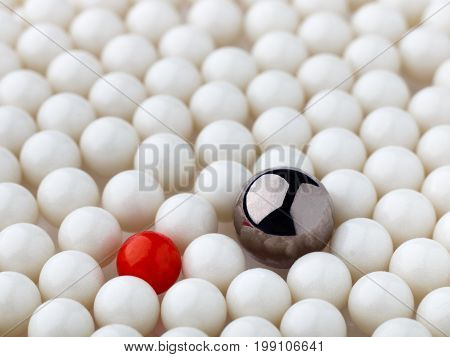 stand out red and metal balls surrounded by white balls. selective focus