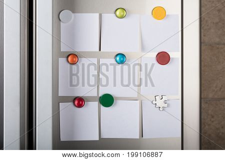 Closeup of blank notes attached with colorful magnetic thumbtacks on metal