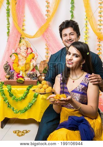 Ganesh Chaturthi - Smart and young Indian couple performing pooja in front of lord ganesh on ganesh festival / utsav, selective focus