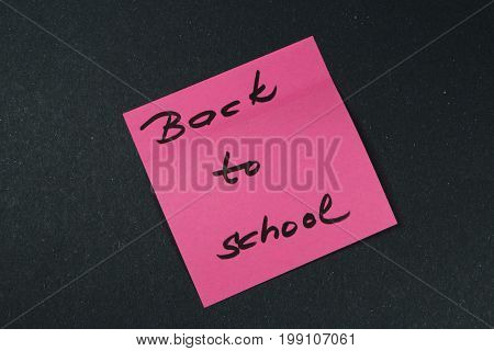 Sign ,,Back to school` on sticker/This is notice ,,Back to school` on black background.