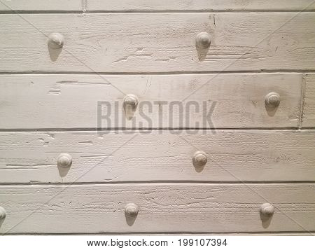 painted white wood wall with metal attachments