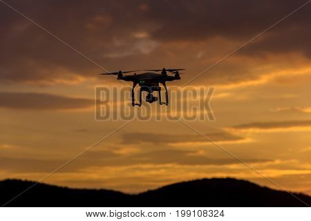 drone quad copter with digital camera at sunset ready to fly for surveillance