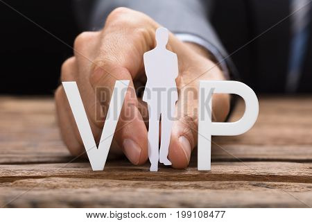 Cropped image of businessman holding paperman forming VIP text on wooden table