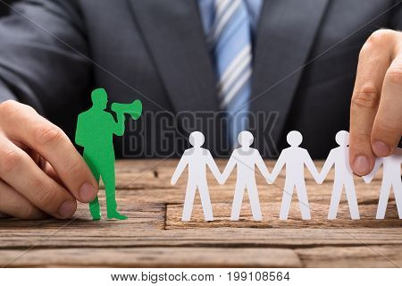 Midsection of businessman holding green paperman speaking through megaphone with team on wooden table