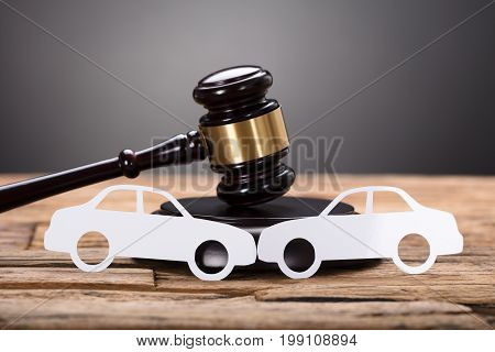 Closeup of paper cars by gavel on wooden table against gray background