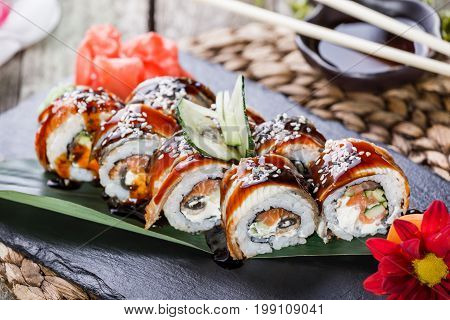 Sushi rolls set with salmon cream cheese cucumber sesame and wasabi on black stone on bamboo mat selective focus. Japanese cuisine