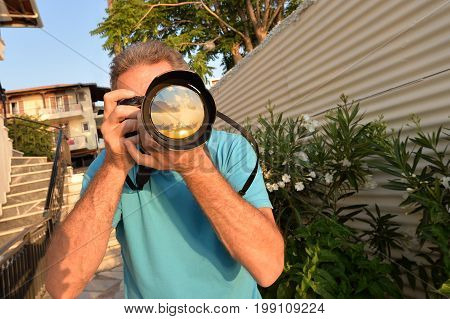 Man holding camera taking pictures at sunrise in Greece, summer holiday
