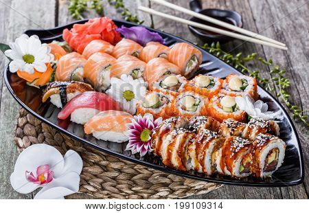 Sushi Set nigiri and sushi rolls decorated with flowers on bamboo background. Japanese cuisine. Selective focus