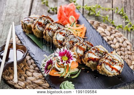 Hot fried Sushi rolls and maki set with smoked eel cream cheese avocado and wasabi on black stone on bamboo mat selective focus. Japanese cuisine