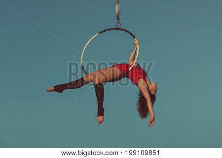 Woman is an aerial acrobat she demonstrates the show on the hoop.