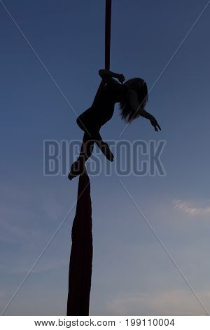 Aerial yoga on a sky background silhouette of a woman.