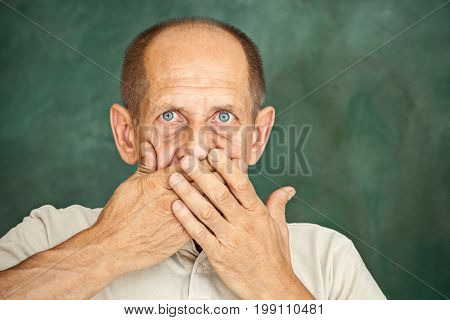 Shocked senior gentleman holding his hand against his mouth and looking at the camera on studio background