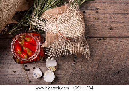 Closeup of piquant red chili pepper in a glass jar, green aromatic twigs of rosemary and empty speckled shells of quail eggs on a wooden table on a light wooden background.