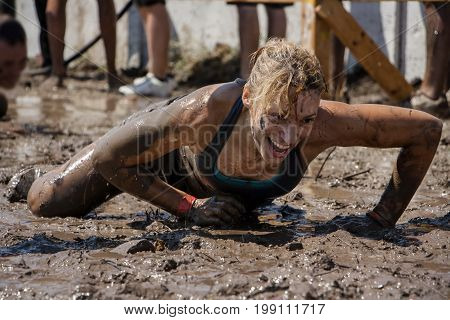 Young woman smiling and crawling under barbed wire; concept of winning endurance strength and fun