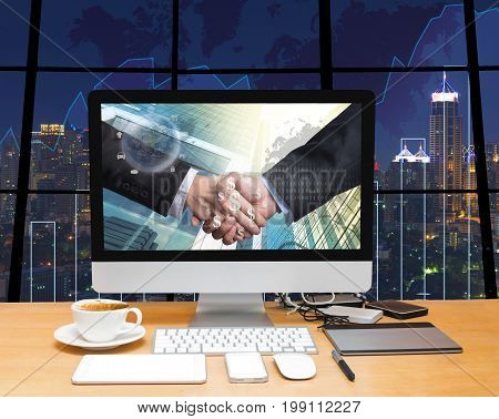 Workspace with computer desktop with Hand shake between businessman at the screen on the trading graph over the blurred photo of cityscape backgroundElements of this image furnished by NASA