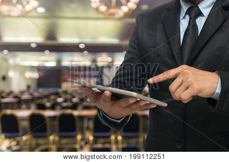 Businessman using the tablet on the Abstract blurred photo of conference hall or seminar room background