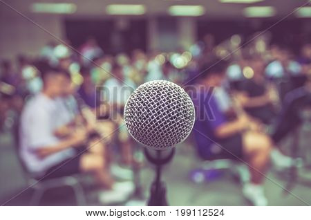 Microphone over the Abstract blurred photo of classic music band when rehearsal musical concep seminar meeting concept