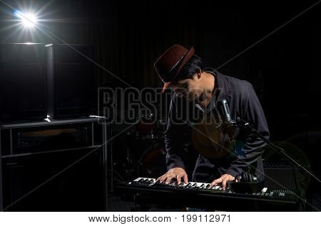 Musician playing keyboard with music instrument and lens flare from spot light on dark background Musician concept