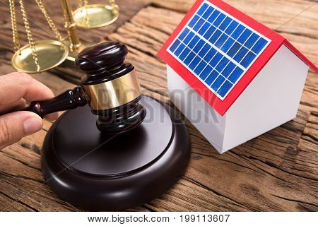 Judge hitting mallet by solar model home and justice scale on wooden table in courtroom