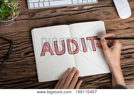 Elevated View Of An Auditor Writing Audit Concept On Notebook