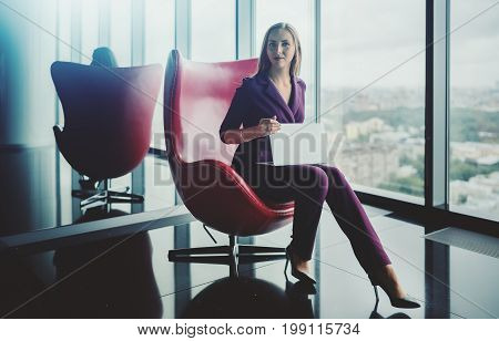 Woman employe in purple suit is sitting on armchair in luxury office holding partly closed net-book and seriously looking into the camera cityscape view from high point in defocused background