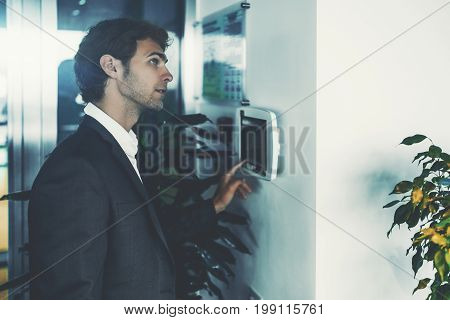 Adult handsome businessman is using terminal of light and air conditioning control placed on white wall while standing in office interior near doors and looking up to see result of his actions
