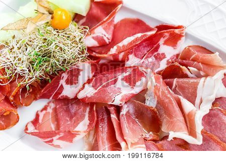 Antipasto platter cold meat plate with prosciutto slices ham salami decorated with physalis and slices of melon on wooden background. Meat appetizer. Top view