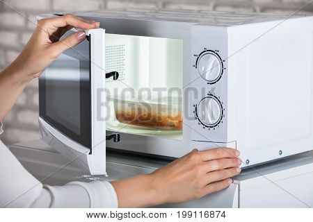 Woman's Hands Closing Microwave Oven Door And Preparing Food At Home