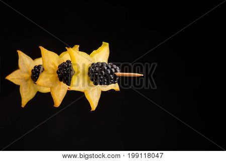 Closeup of juicy blackberries on a stick with yellow sappy healthy-giving carambola, fruits for tasty refreshing salads and dishes on a dark black background. Star-shaped fruit.
