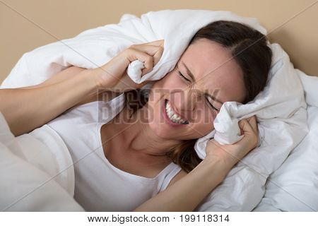 Troubled Woman In Bed Covering Ears To Shut Out Noise