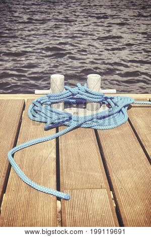 Retro Toned Picture Of A Cleat With Blue Rope On A Wooden Pier.
