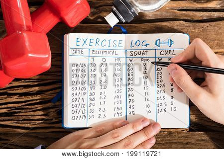 Elevated View Of A Hand Filling Exercise Log On Notebook With Exercise Equipment On Desk