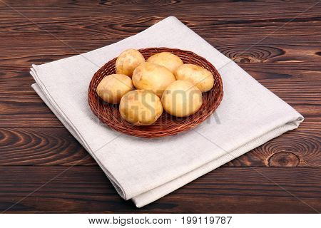 New and raw potatoes in a wattled plate, young unpeeled potatoes for delicious courses, vegetables containing substances necessary for growth, health, and good condition on a dark brown background.