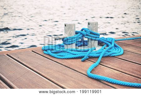 Cleat With Blue Rope On A Wooden Pier.