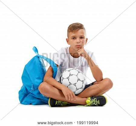 A boy with a ball. A little schooler sitting in the lotus position isolated on a white background. A sportive kid with bright satchel and soccer ball. Sports concept. Championship concept.