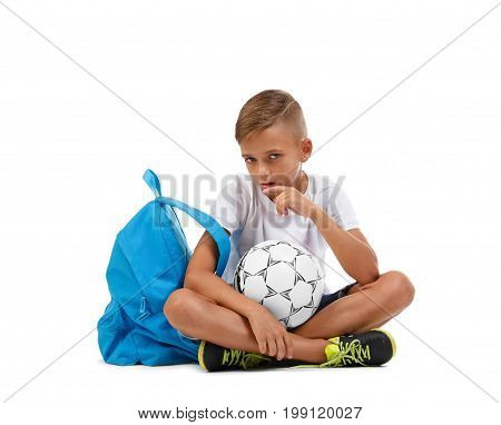 A little schooler sitting on the ground in the lotus position isolated on a white background. A sportive kid with bright satchel and soccer ball. Sports concept. Childhood concept.