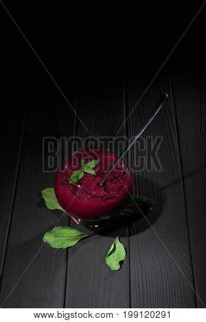 A composition of a healthful vegetable claret-colored snack with a metal spoon surrounded with green beet leaves. A big glass filled with grated beetroot on a black table background. Copy space.