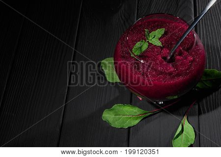 A big glass filled with grated beetroot on a black table background. A composition of a healthful vegetable claret-colored snack with a metal spoon surrounded with green beet leaves. Copy space.