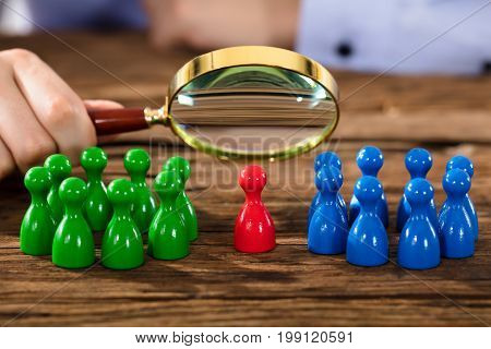 Close-up Of A Person's Hand Examining Figures With Magnifying Glass Over Wooden Desk