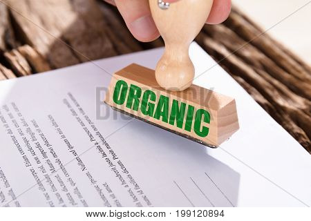 Close-up Of A Green Organic Stamp On Document Over Desk